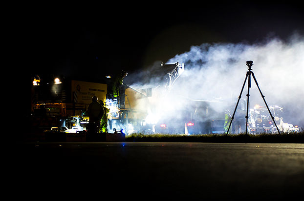 Camera on tripod filming a construction site at night